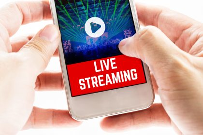 Close up Two hand holding mobile phone with live streaming word and concert event, Digital Marketing concept.